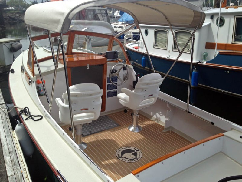 Cockpit with pedestal seats and synthetic teak flooring.