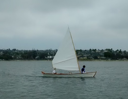 Sharpie skiff under sail.