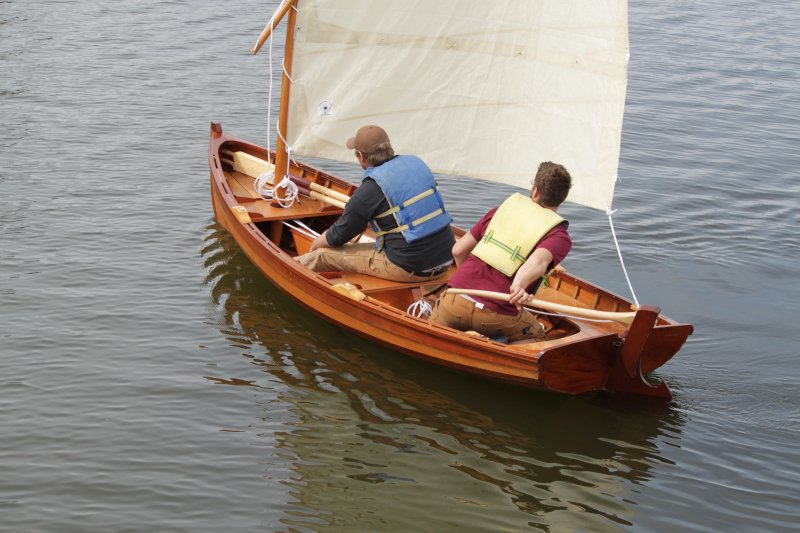 The slender lapstrake Sid skiff has a sprit rig