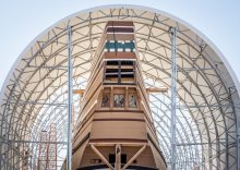 "MAYFLOWER II's stern peeks out from underneath the temporary structure nicknamed ""the Mailbox."""