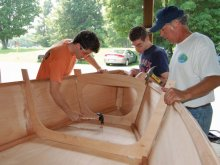 Three family members help to build wooden boat.