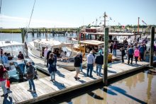 Wooden boats in the water, come aboard and chat with builders and owners