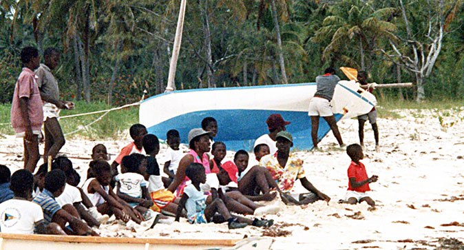 Bahamian fishing sloop beached for painting
